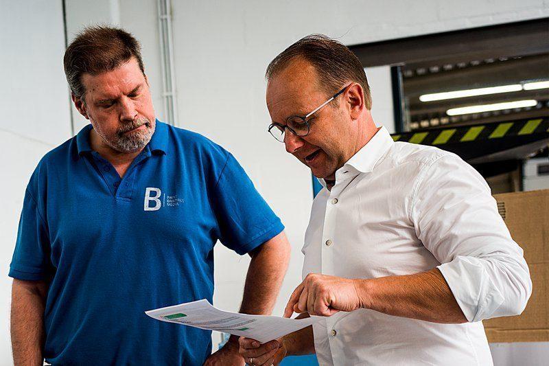 Collega Kris bespreekt een project met drukker Werner