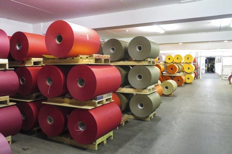 De productiehallen in de Gmund Fabriek in Oostenrijk. Rood, bruin, oranje en geel papier ligt op grote rollen klaar. Kwalitatief en ecologisch papier