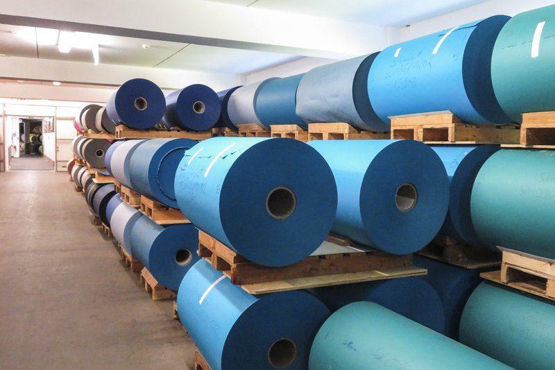 De productiehallen in de Gmund Fabriek in Oostenrijk. Verschillende tinten blauwn papier ligt op grote rollen klaar. Kwalitatief en ecologisch papier