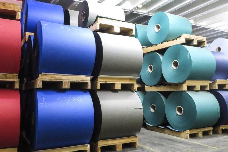De productiehallen in de Gmund Fabriek in Oostenrijk. Rood, grijs, blauw, en groen  papier ligt op grote rollen klaar. Kwalitatief en ecologisch papier