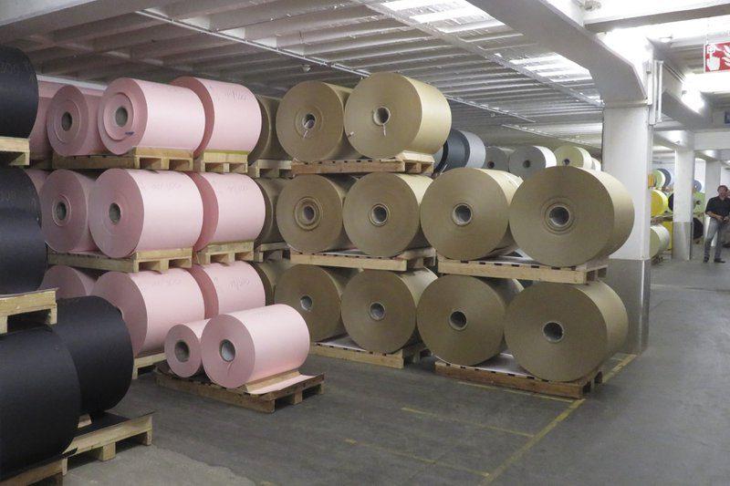 De productiehallen in de Gmund Papierfabriek in Oostenrijk. Zwart, roze en bruin papier ligt op grote rollen klaar. Kwalitatief en ecologisch papier