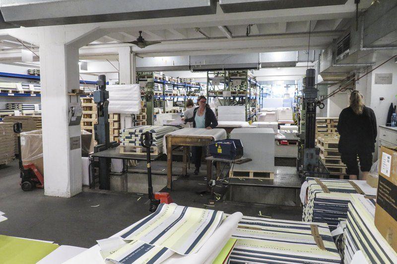 Vrouwen werken in de fabriek van Gmund. Ze pakken het afgewerkte papier in, in het typerende inpakpapier van de papierfabrikant. Gmund is kwalitatief en ecologisch papier.