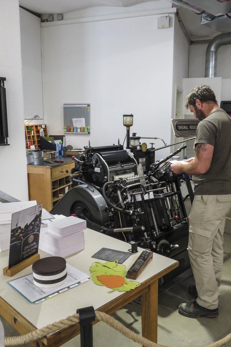Een werknemer van de Papierfabrikant Gmund staat aan de Heidelberg drukpers om te werken met oude druktechnieken op Gmund papier.