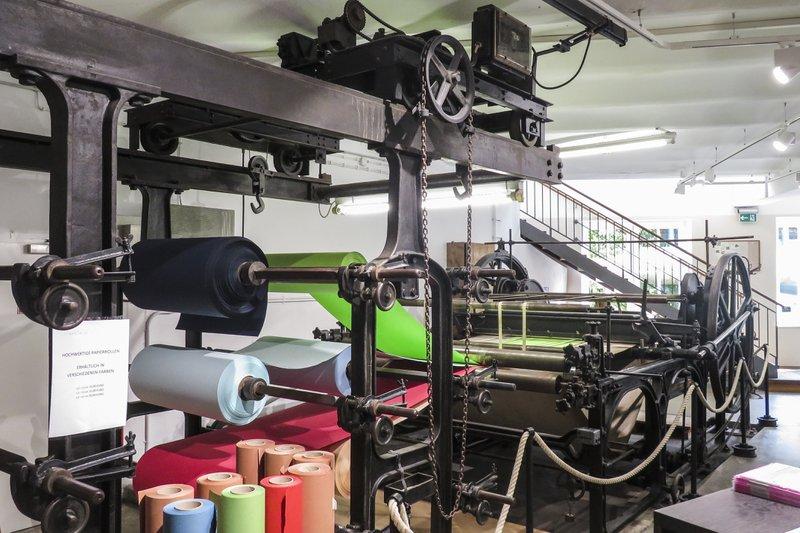 Een oude papiermachine waarop papieren rollen zijn uitgerold als voorbeeld van het proces van het maken van papier in de Gmund Papierfabriek in Oostenrijk.