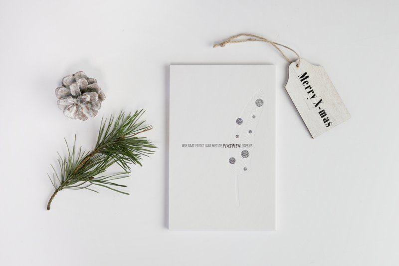 Kerstkaart als teaserkaart met glitter als foliedruk en een veer als blinddruk aan de voorkant van de kaart.