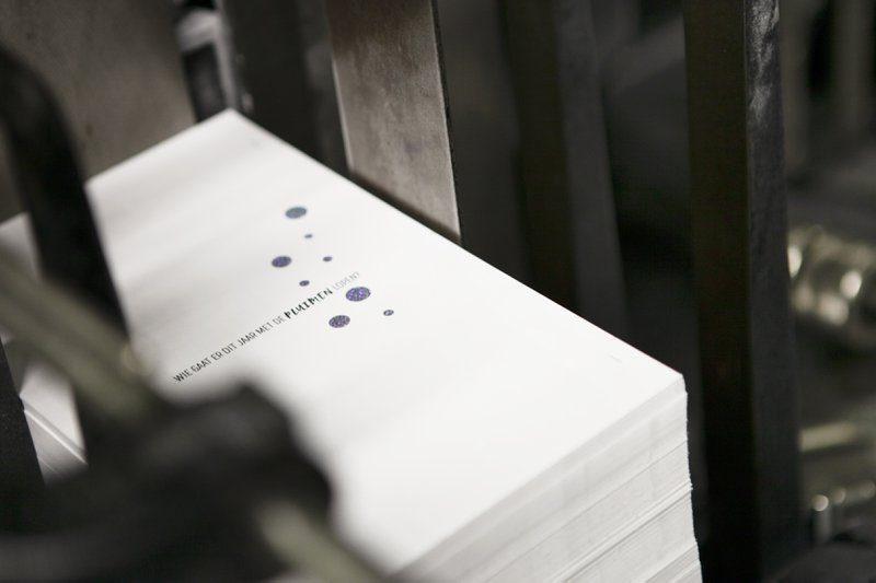 Wit papier met zilver, glitter foliedruk en een veer als diepdruk. Een speciale afwerking voor eindejaarsdrukwerk