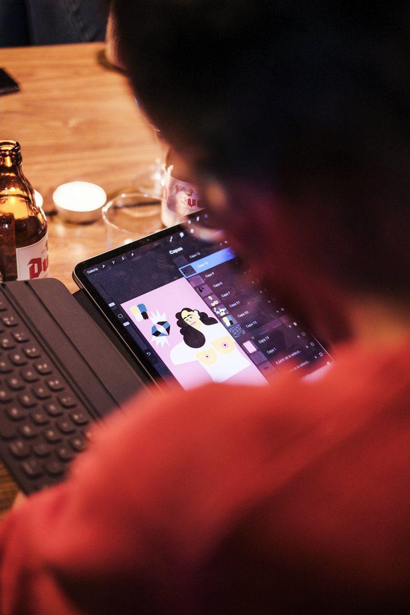 Designer is via zijn tablet zijn designs aan het klaarmaken. Aan het digitaliseren van illustraties zodat het klaar gemaakt kan worden voor het DATE Antwerp kunstboek