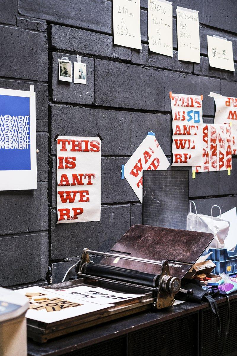 Behind the scenes van het maken van het boek DATE Antwerp van This is Antwerp. Posters hangen tegen de muur met tape als overzicht