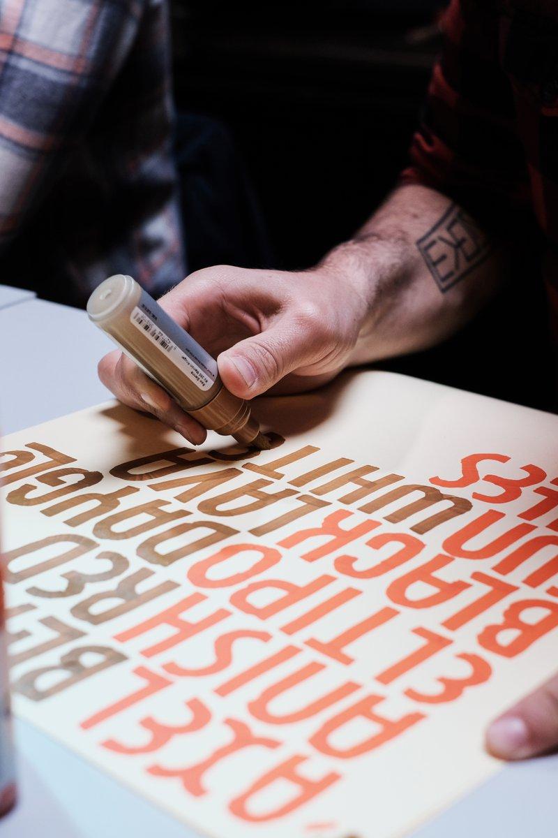 Designer schrijft typografische tekst op papier met speciale pen.